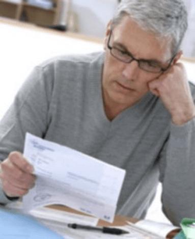 Homme en pull gris regardant sa facture