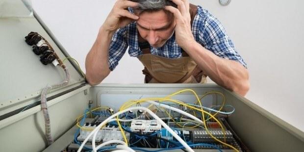 Homme se tenant la tête au dessus d'un compteur électrique